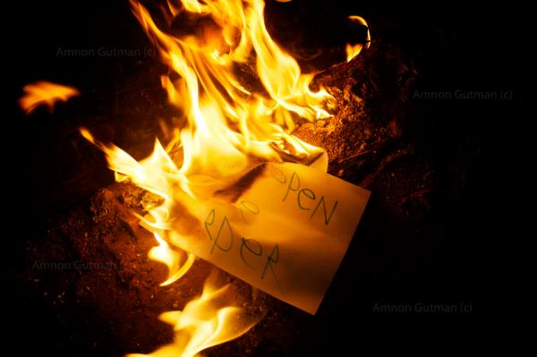 """Refugees burning a sign saying """"open the border"""" , in order to keep warm, after a peaceful demonstration outside of Belgrade train station."""