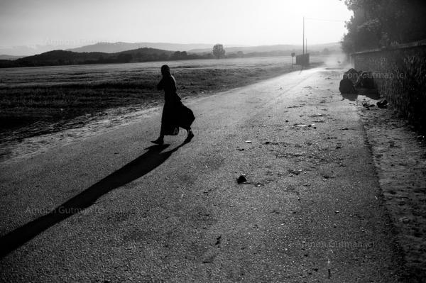 A refuge walks inside the camp, during a morning sand storm.