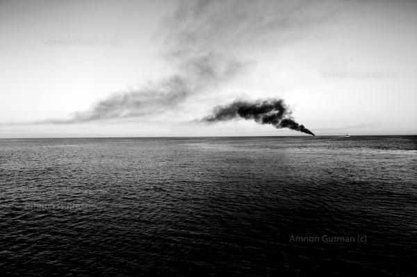 Smoke rises from burnt rubber boats. the Italian navy burns all rubber boat that were used to carry refuges and migrants from the Libyan coast, in order not give smugglers the opportunity to reuse them again.
