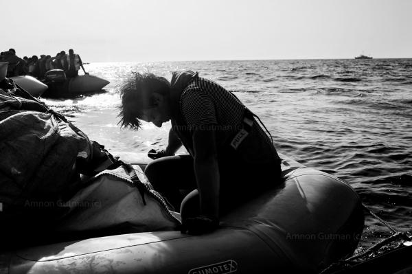 A member of Sea Watch crew, takes a very short break, after delivering life vests to refuges and migrants on one boat out of four that were rescued by Sea Watch that morning.