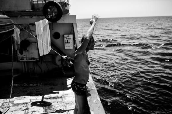 A member of Sea Watch, washing himself with water after a long day of refugees rescues off the Libyan cost.