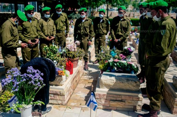 IDF soldiers , paying their respect to a woman whose son fell during his army service, on Memorial Day, two months after the pandemic started.