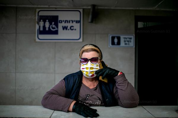 A woman talking over the phone, while keeping a public urinal clean. at the vegetable market, in the city of Beer Sheva.