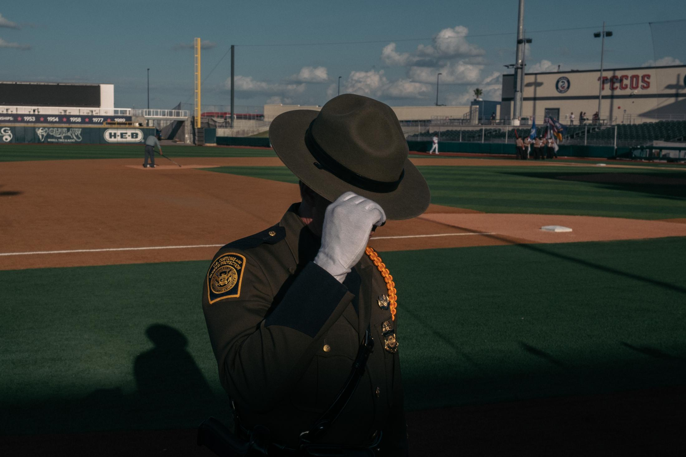 Border Patrol Agent Joshua Steele prepares to sing the U.S. national anthem before a baseball game at Laredo's Uni-Trade Stadium. Shot on assignment for L'EQUIPE. Laredo, Texas, United States, May 2021.