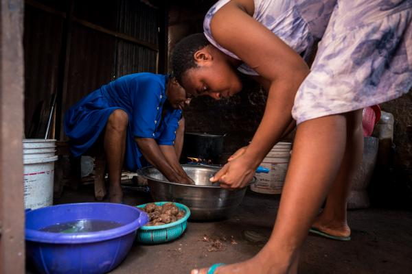 As Mercy prepares to make lunch, her first child, Chinaza helps out in the kitchen.