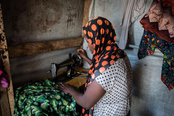 Farida*, works on a client's dress in her home in Maiduguri. Farida* is one of several women that has greatly benefitted from UNFPA interventions. A few months into the year 2020, she received a sewing machine from UNFPA.