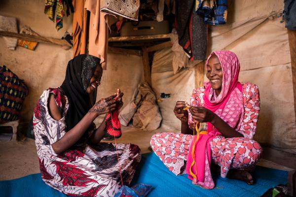 Hurairah* and her mother share a laugh while knitting baby accessories for sale in their home in Maiduguri.