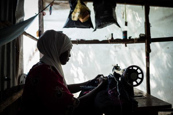 Fara*, works on her dress in her tent in Maiduguri.