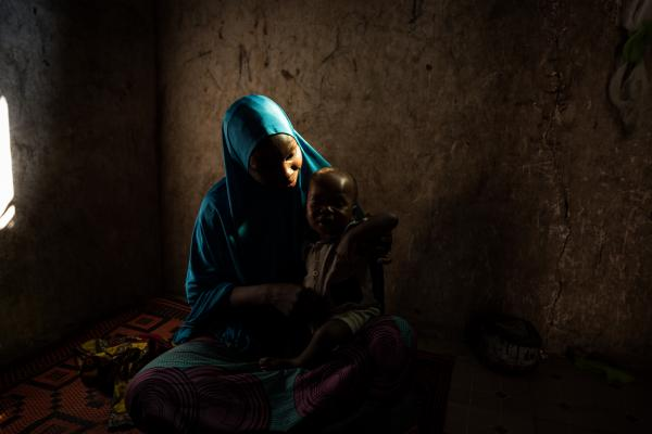 Hamida* plays with her youngest child in their home in Maiduguri.