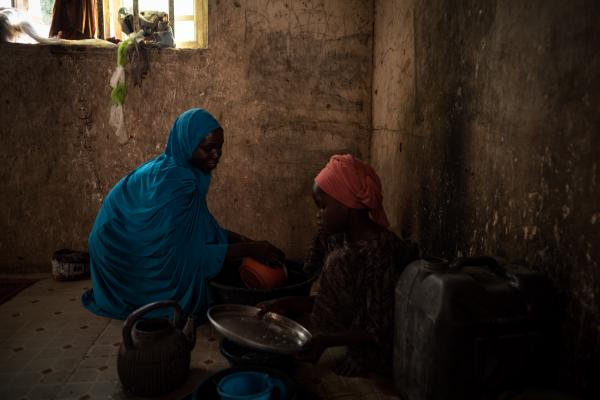 Hamida* and her eldest child, carry out some household chores in their home in Maiduguri.