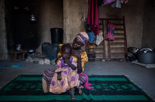 Jamila*, 35, plays with her youngest child in their room in Maiduguri.