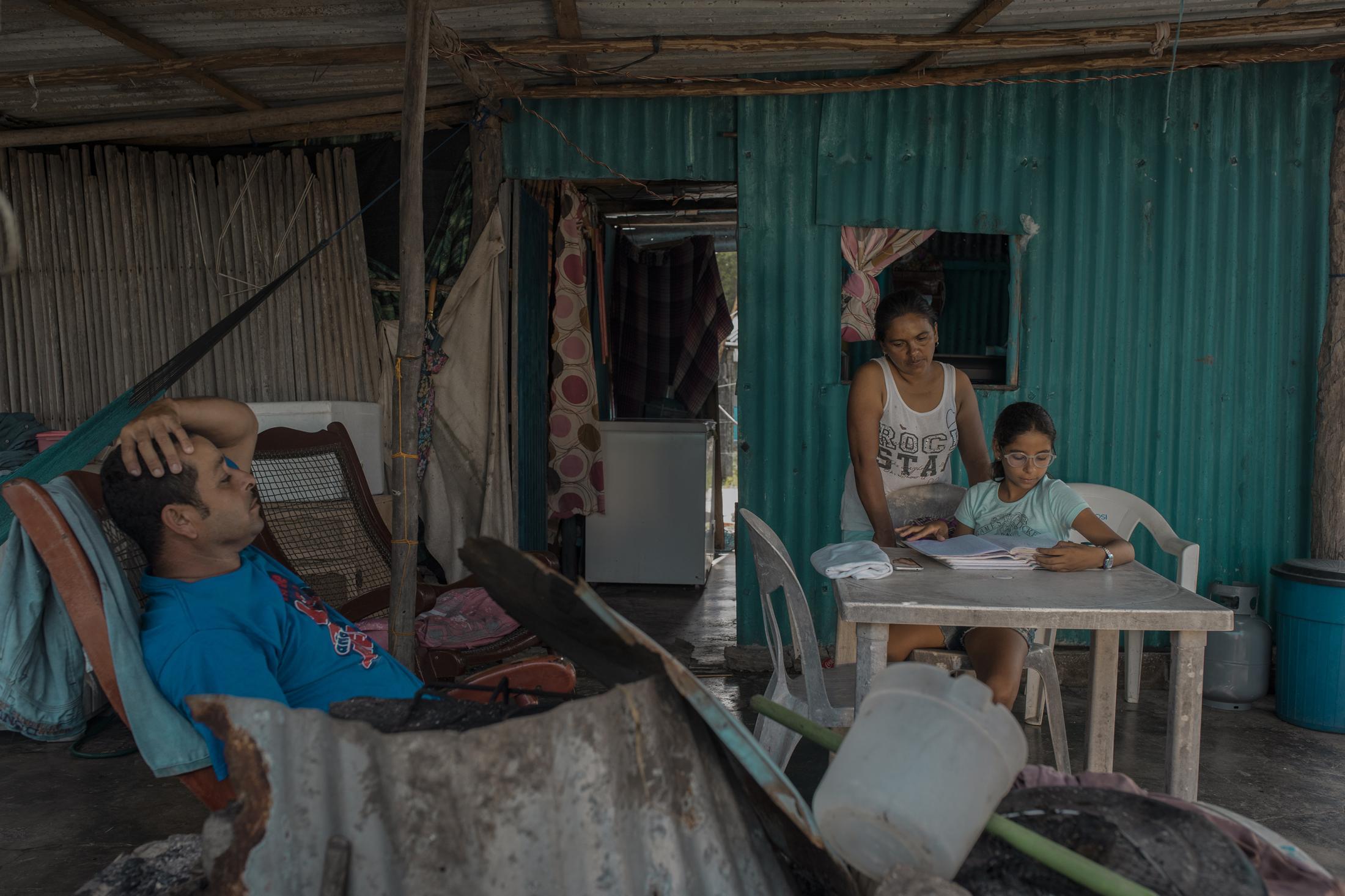 Sara Chavez, 11 años, repasa sus tareas con ayuda de sus madre en la vivienda de la comunidad de Costa de San Juan, Alvarado. Sara ha sido una de las estudiantes afectadas por la pandemia del Covid-19 al vivir en una comunidad sin energía eléctrica ni internet para poder realizar sus actividades académicas.
