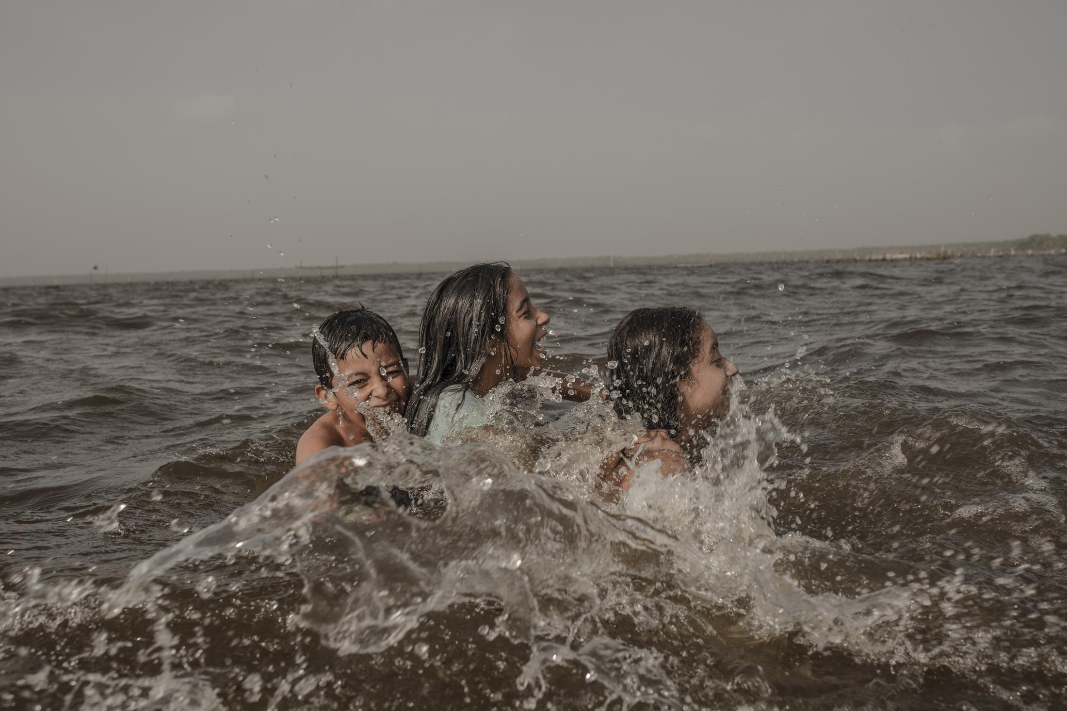 Sara Chavez, 11 años, juega en la laguna de Alvarado con su amiga Maria Fernanda y Josué en la pequeña comunidad de Costa de San Juan, Alvarado. Sara ha sido una de las estudiantes de primaria afectadas por la pandemia del Covid-19 al vivir en una isla sin energía eléctrica ni internet para poder realizar sus actividades académicas.