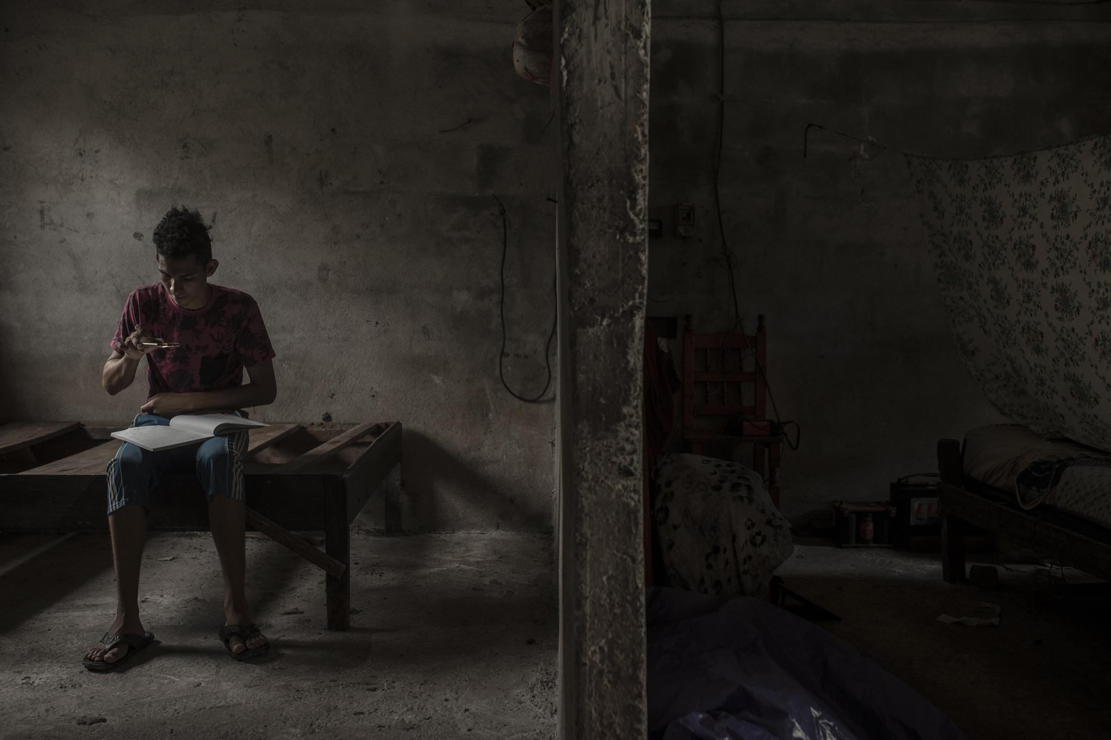 Brian Zamudio, 18 años, toma una fotografía a su tarea al interior de una vivienda de la comunidad de El Nacaste, Alvarado. Brian ha sido uno de los estudiantes afectados por la pandemia del Covid-19 al vivir en una comunidad sin energía eléctrica ni internet para poder realizar sus actividades académicas.