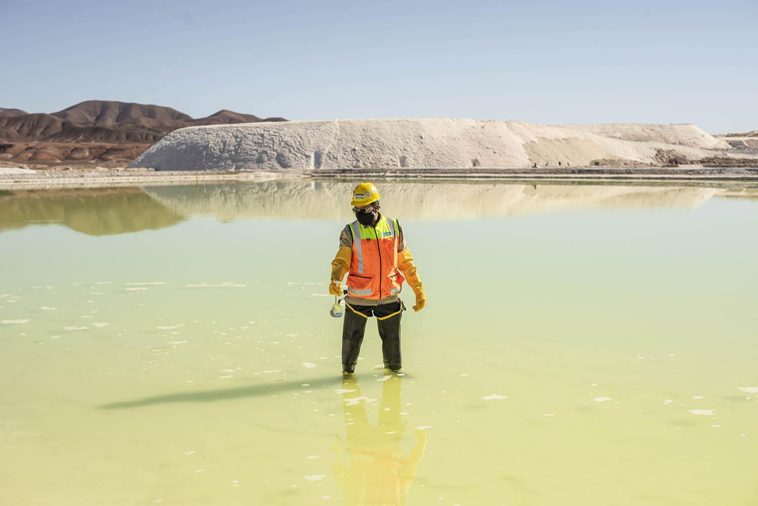 A mine worker takes samples from a brine pool at the Albemarle plant in the Atacama Desert, Chile. 2021