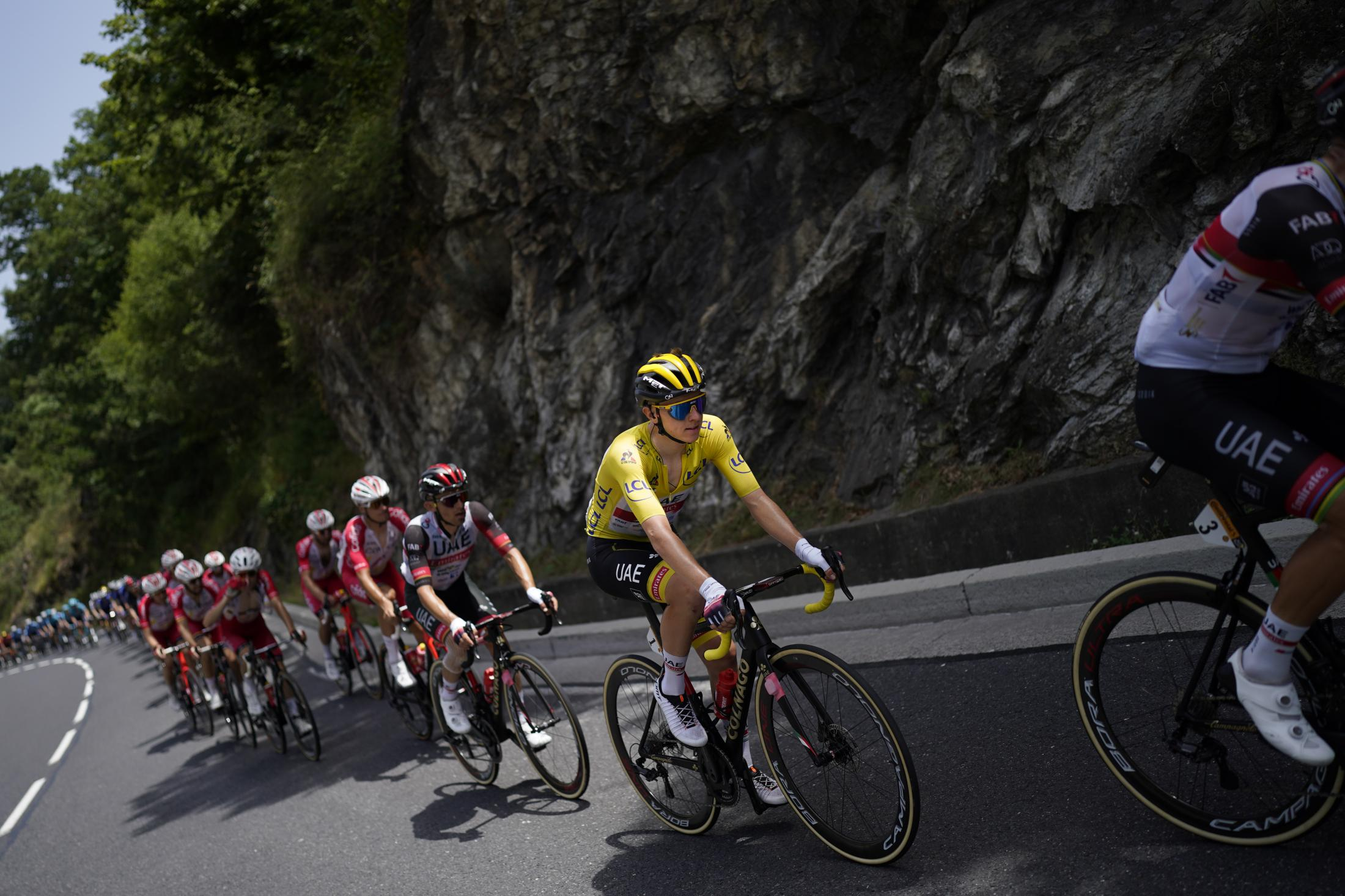The pack with Slovenia's Tadej Pogacar, wearing the overall leader's yellow jersey, climbs during the fifteenth stage of the Tour de France cycling race over 191.3 kilometers (118.9 miles) with start in Ceret, France, and finish in Andorra-la-Vella, Andorra, Sunday, July 11, 2021. (AP Photo/Daniel Cole)