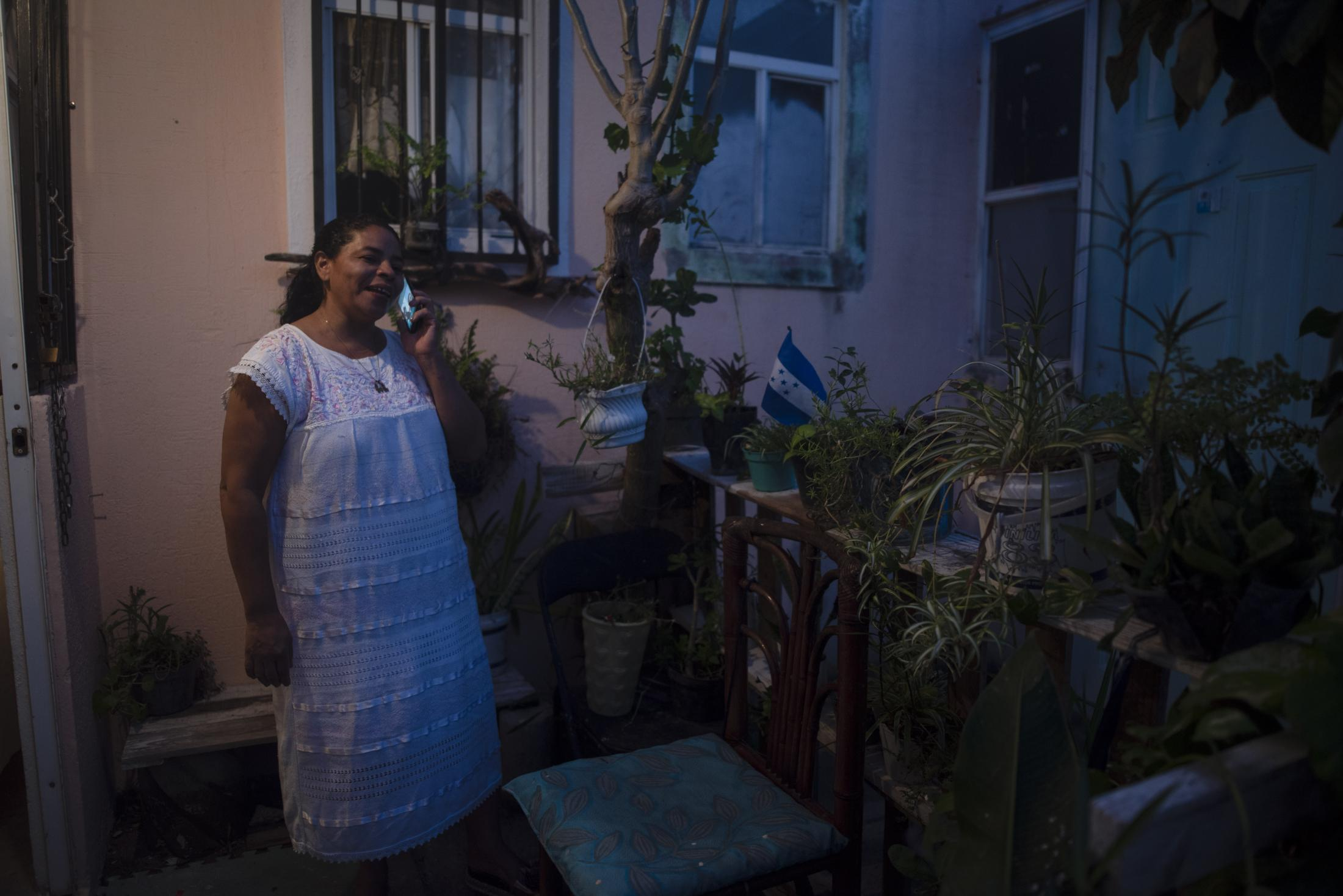 Paola Reyes habla por teléfono con un familiar en Honduras, desde el jardín de su casa, en Medellín de Bravo, Veracruz, México. El 18 de Noviembre del 2020.