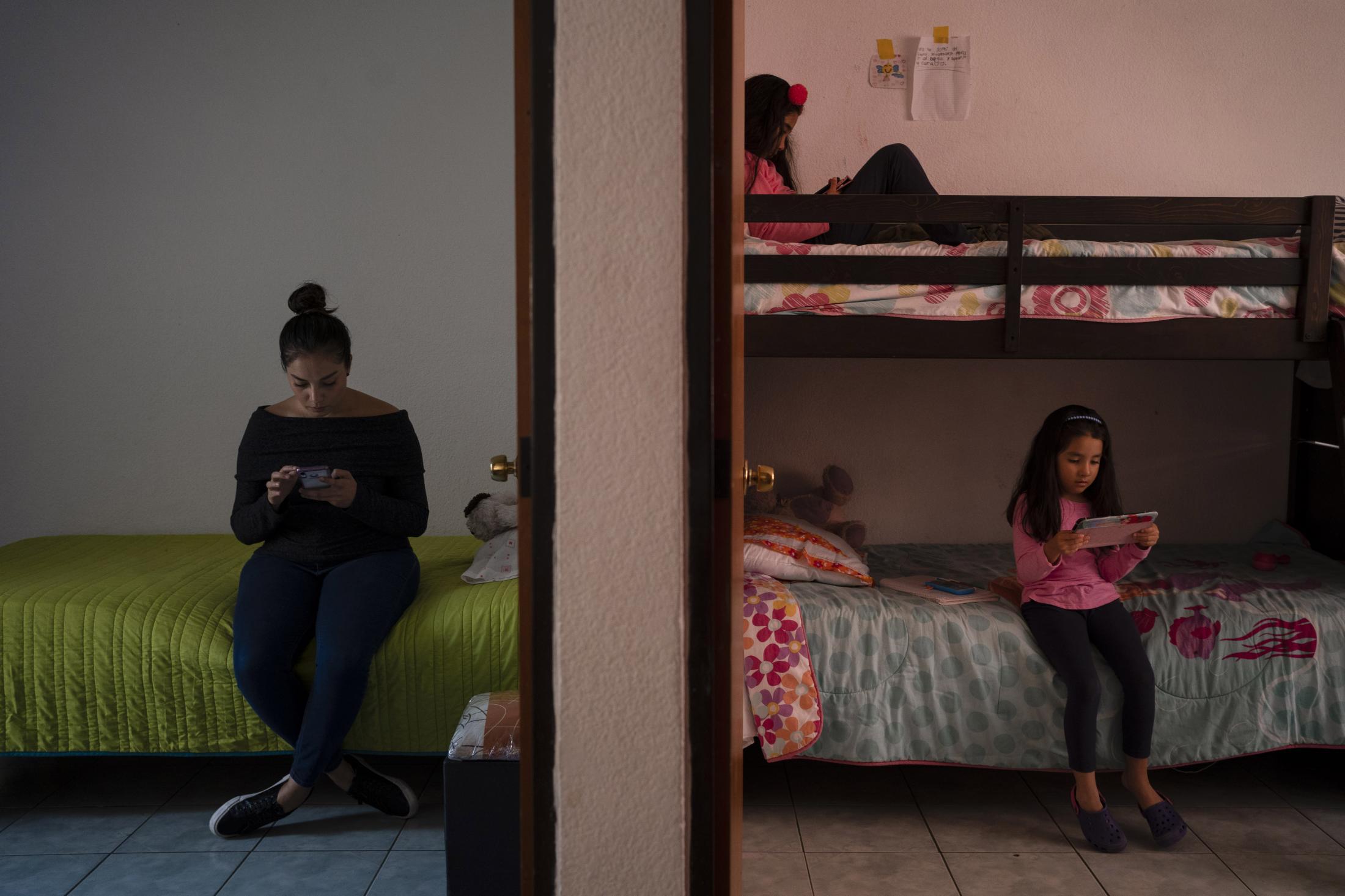 Mónica Quijano trabaja recibiendo pedidos de productos a través de su página de Facebook, mientras sus hijas juegan en sus tabletas digitales, al interior de sus respectivas habitaciones. En San Luis Potosí, México. El 3 de Diciembre del 2020.