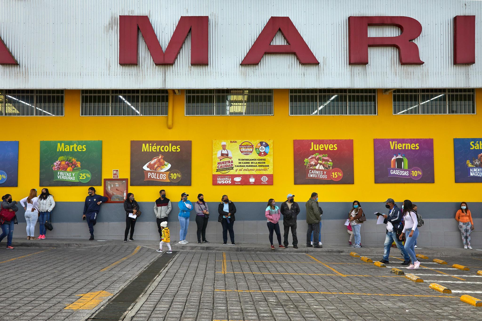 ESP: Personas migrantes, de Venezuela y Haití, hacen fila en las afueras de un supermercado a la espera de ayuda humanitaria para adquirir alimentos. Quito, Ecuador. Noviembre 2020. _ EN: Migrants, from Venezuela and Haití, line up outside a supermarket waiting for humanitarian aid to provide food. Quito, Ecuador. November 2020.