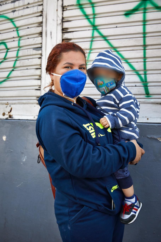 ESP: Retrato de una mujer migrante junto a su bebé. Están a la espera de recibir ayuda humanitaria para adquirir alimentos. Quito, Ecuador. Noviembre 2020.  EN: Portrait of a migrant woman with her baby. They are waiting for humanitarian aid to buy food. Quito, Ecuador. November 2020.