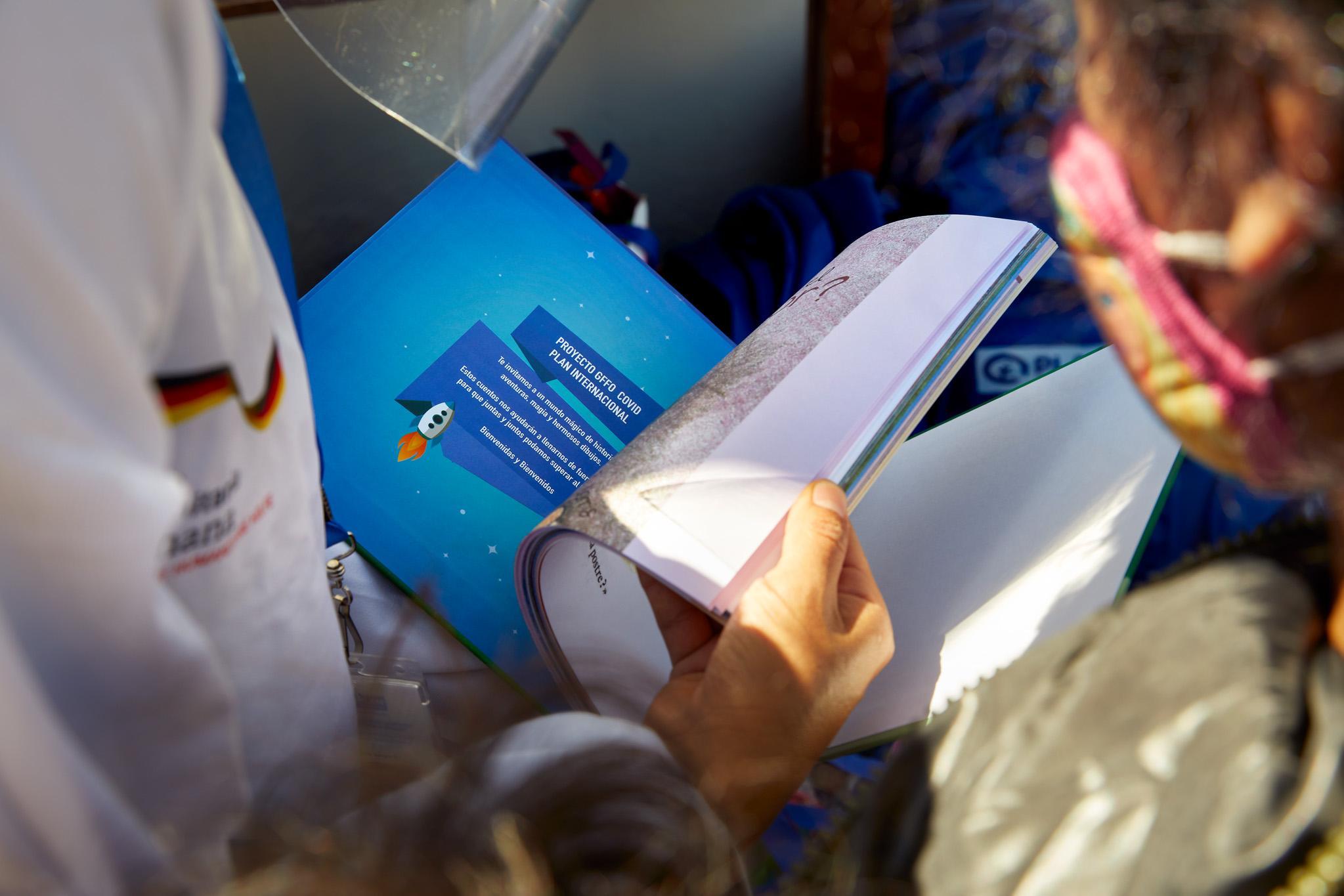 ESP: Diana Obando, psicóloga del Proyecto GFFO de Plan Internacional, muestra a una pequeña niña beneficiaria el contenido del cuento entregado junto al kit de juguetes. Quito, Ecuador. Diciembre 2020.  ENG: Diana Obando, psychologist of the GFFO Project of Plan International, shows a little girl who is a beneficiary the content of the story delivered with the toy kit. Quito, Ecuador. December 2020.