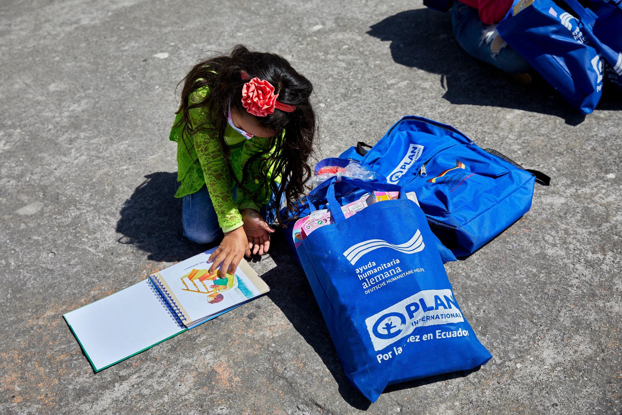 ESP: Una pequeña niña revisa el cuento que le han entregado en la jornada de donación de kits de juguetes. Quito, Ecuador. Diciembre 2020.  ENG: A little girl reviews the story she was given at the toy kit donation day. Quito, Ecuador. December 2020.