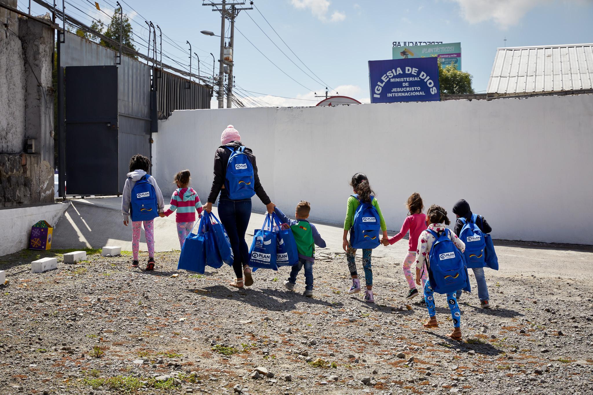 ESP: Una mujer migrante y varios niños se despiden de la jornada de donación de kits de juguetes. Quito, Ecuador. Diciembre 2020.  ENG: A migrant woman and several children say goodbye to the toy kit donation day. Quito, Ecuador. December 2020.