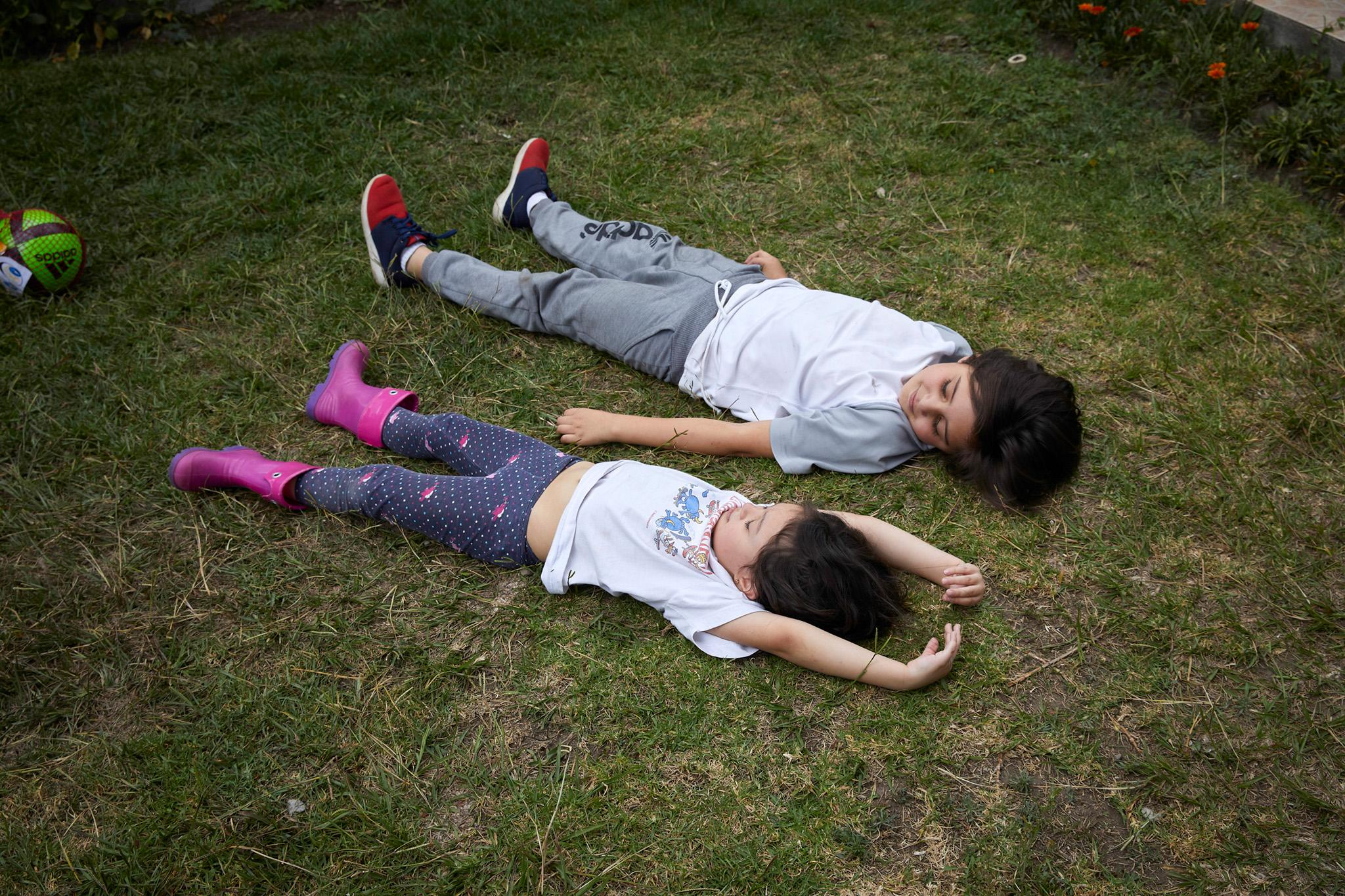 Helena and Gerardo, 6 and 9 years old, rest in the patio of their house after having played with their father Rafael. Both have been studying at the Educational Foundation Centro del Amanecer for 2 years when they came with their parents from Venezuela. Their mother, Xioralbys, is an educator at the same school. Gerardo has TDH and has always had a hard time in other schools, which is why his parents sought a different education for their children when they arrived in Ecuador. Tumbaco, Ecuador.