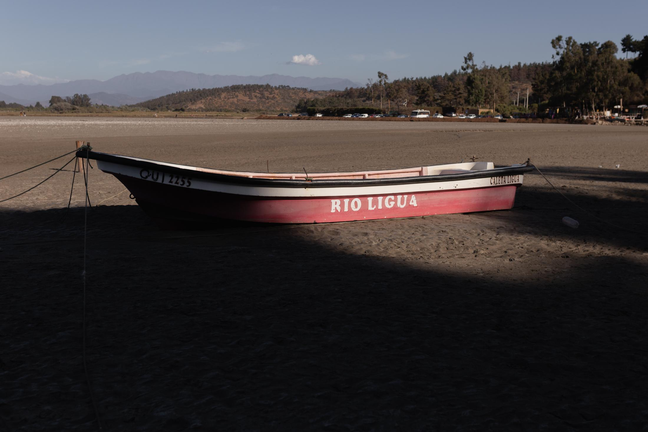"""December, 12, 2020.A boat named """"Río Ligua"""" is seen on Las Salinas beach, 20 km from La Ligua, on the coast of the province. The Ligua and Petorca rivers were declared depleted in 2004 and 1997 respectively, when the avocado industry began to monopolize surface and underground water rights of both rivers, a situation generated by the policies established in the Chilean Water Code of 1981, which allows the privatization of water and its indiscriminate exploitation without being clear about the availability of water in the basins."""