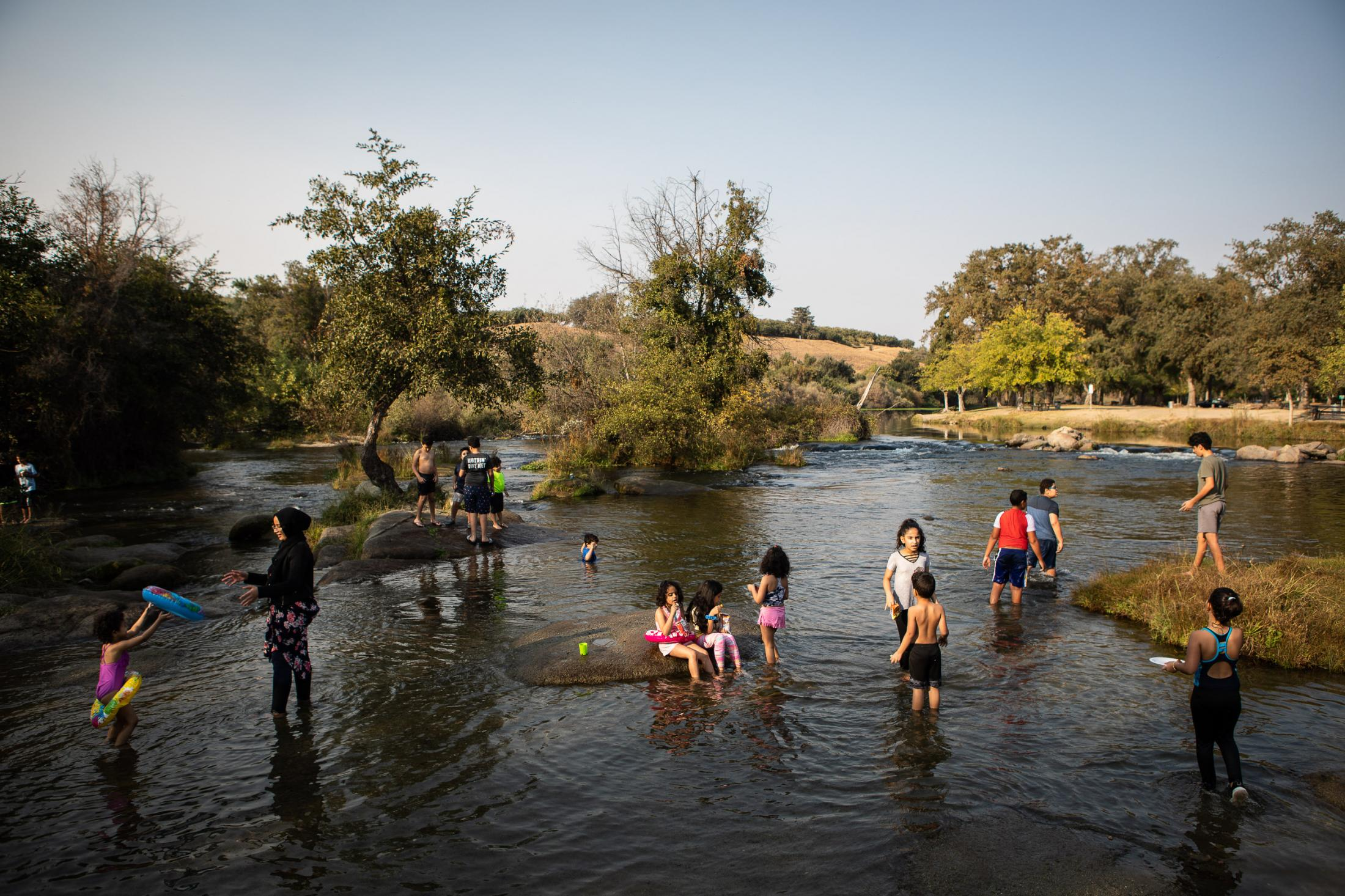 Children swim in the San Joaquin river on a hot October day. The San Joaquin River is California's second-longest waterway, fed by snowmelt from the Sierra Nevada Mountains. From Friant dam it is divvied up and shunted into a vast network of canals to supply water for millions of acres of farmland and the Central Valley's growing cities. For decades, one 60-mile section—beginning 38 miles downstream of Friant Dam and stretching to the San Joaquin's confluence with the Merced River—ran dry. Parts of the river where water still flowed were blighted with pesticides and fertilizer, creating massive algal blooms and dead zones. The intensive engineering of the river exacted a huge toll on its native ecosystems. No species suffered more than the Chinook salmon, whose epic migration from the Pacific Ocean to its spawning grounds in the High Sierra was cut short by numerous choke points, not the least of which was Friant's impenetrable barrier of concrete. In a resent settlement mandated that a mere fraction of the San Joaquin's historic flow be restored. The river's many dams would remain, but alternative passages would be built and new spawning areas added in the lower river. In other words, the settlement sought to give the salmon a chance to survive within a massive water management scheme that favors industrial-scale farming. Photographed on assignment for Sierra Magazine