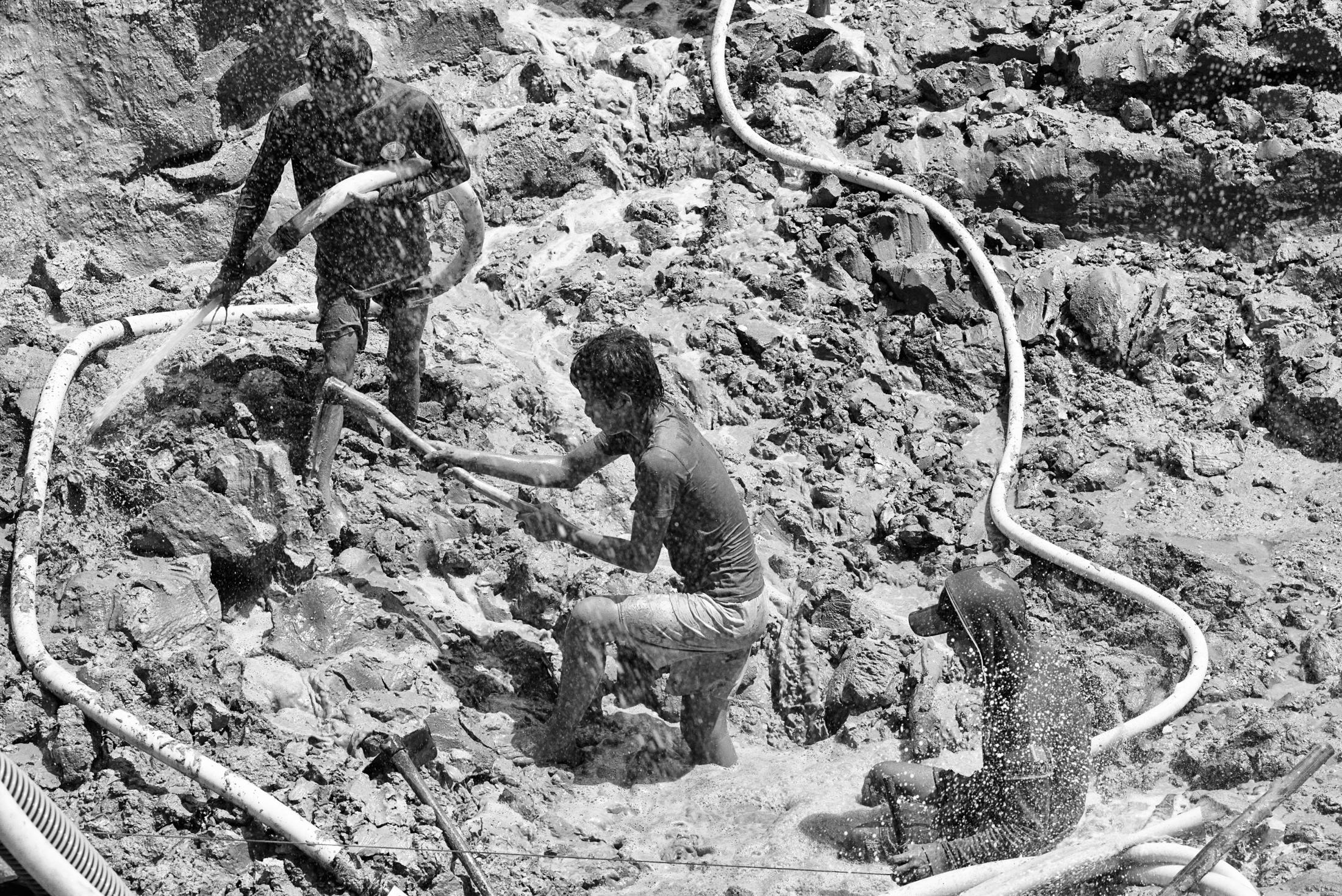 Illegal tin miners work at an abandoned open pit at Air Anyir in Bangka Island, Indonesia, on May 9, 2016.