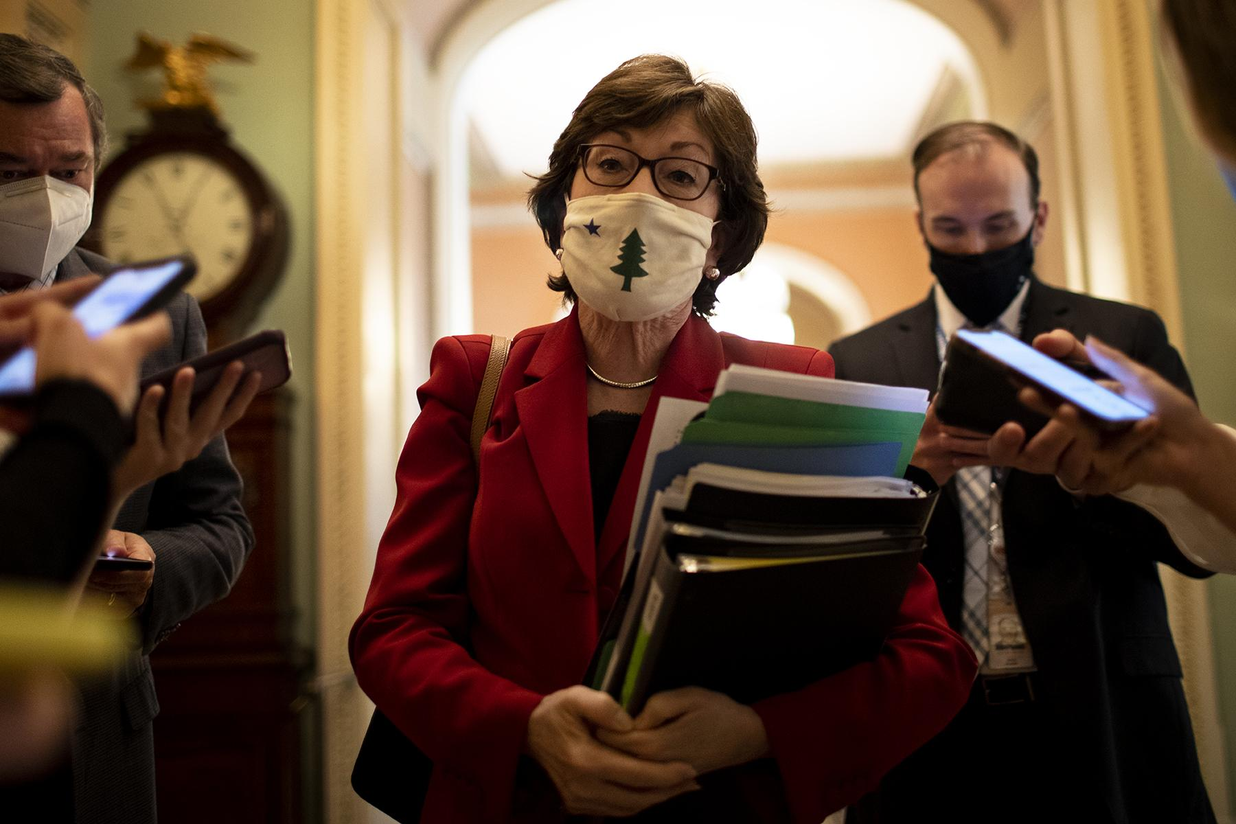 Senator Susan Collins walking in the US Capitol takes questions while the Senate debated in infrastructure bill on August 5.