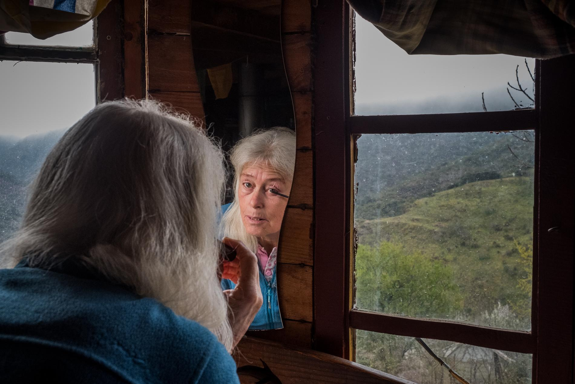 Hannah Brüderer brings on make-up in a wooden yurt in Matavenero, Spain. She is among the founders of the village, where she brought up her two children. She still has a house in the village and visits the community regularly, a.o. to visit her son and grandchildren. Matavenero, 3-4-2021