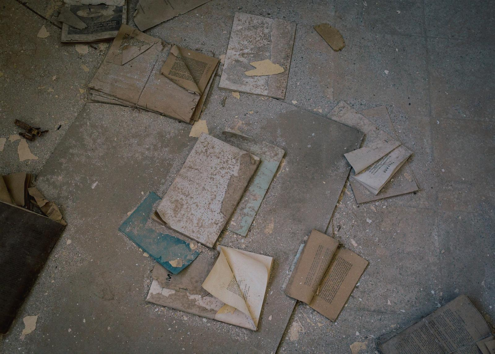 Books lie scattered on the floor in the former library in the ghost town.