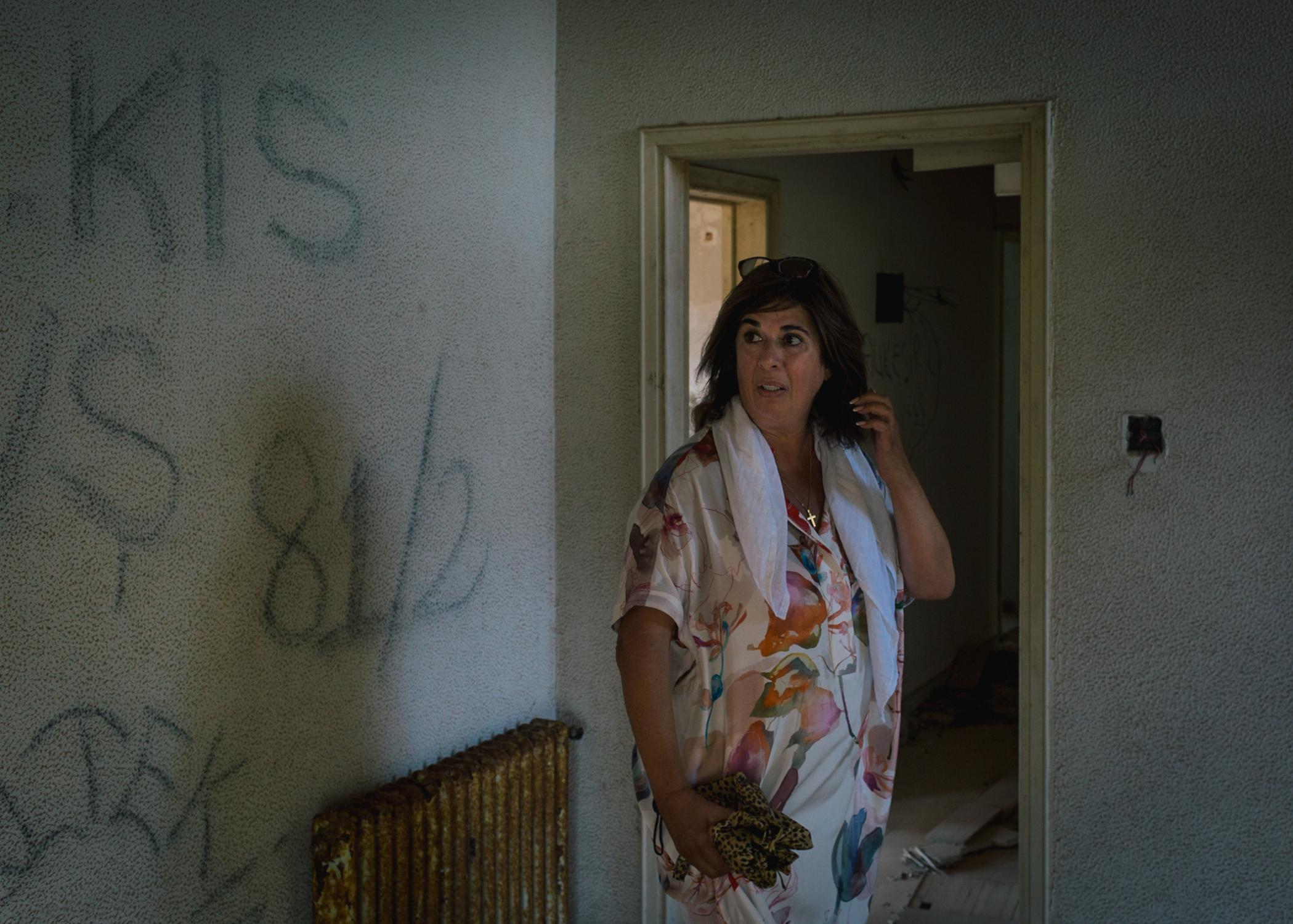 Tasoula Hadjitofi in an abandoned building in ghost town Varosia, searching for her home from which she fled as a 15-year-old girl in 1974.