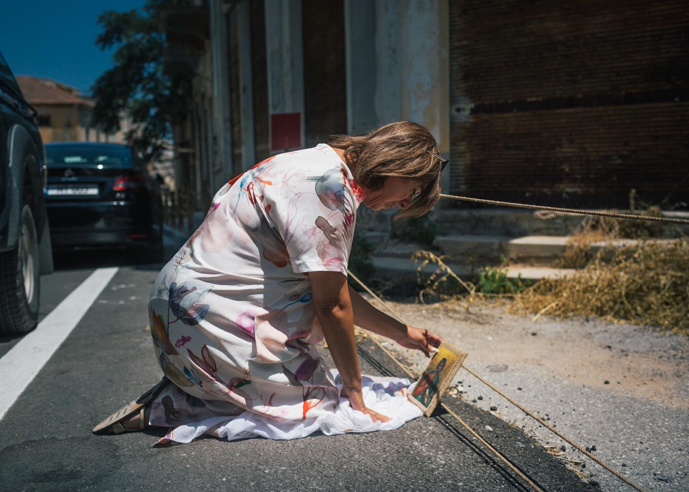 Tasoula Hadjitofi prays in front of the barrier of a former church in the ghost town, as a protest against the visit of President Erdogan.