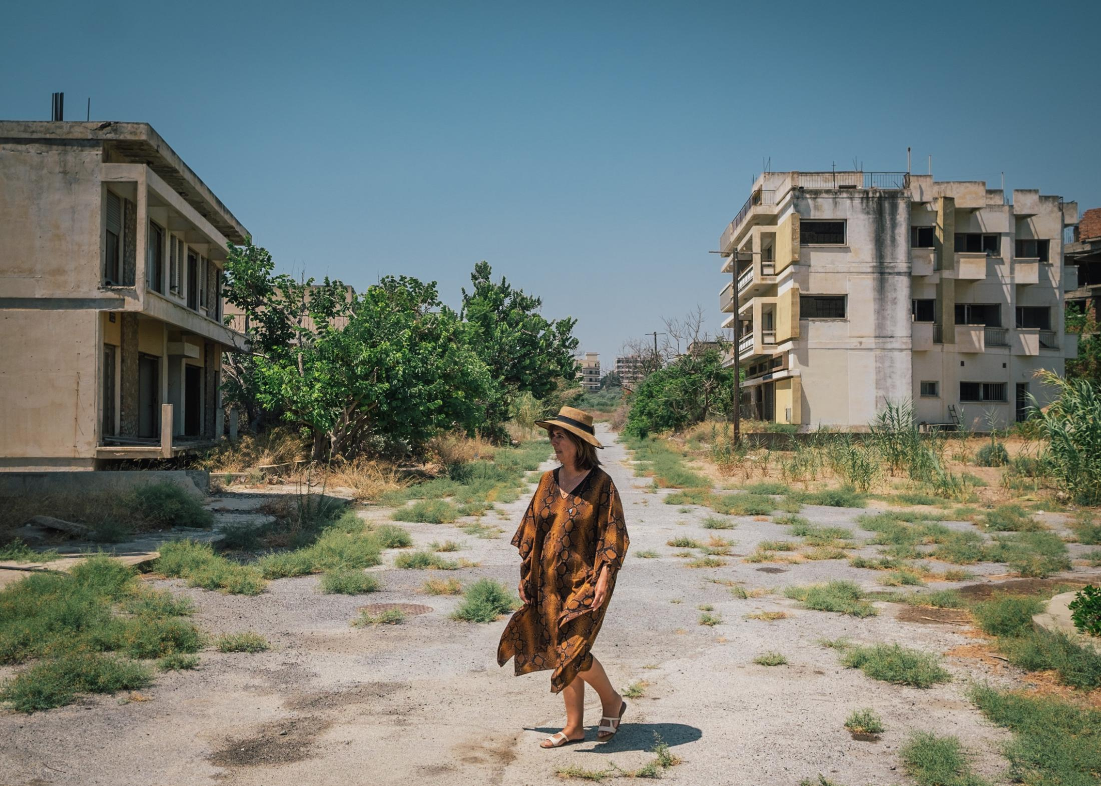 Tasoula Hadjitofi stands on a closed road in the ghost town of Varosia, which leads to her former home from which she fled as a 15-year-old girl.