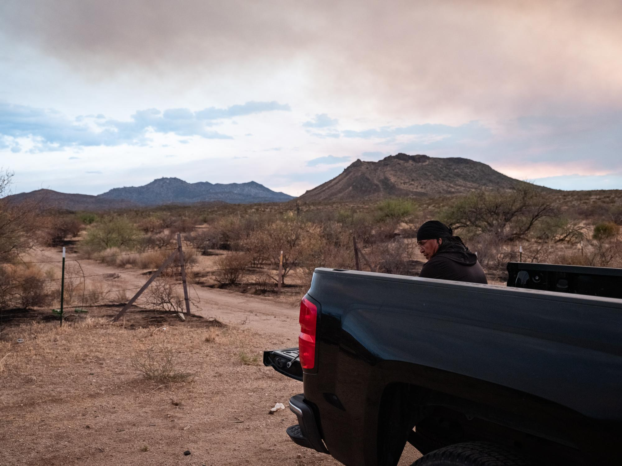 Dr. Wendsler Nosie Sr sits in the back of his truck on the San Carlos Apache Reservation following one of his daily runs to train for the Mt. Graham Sacred Run, with smoke in the air from the Mescal Fire raging nearby.