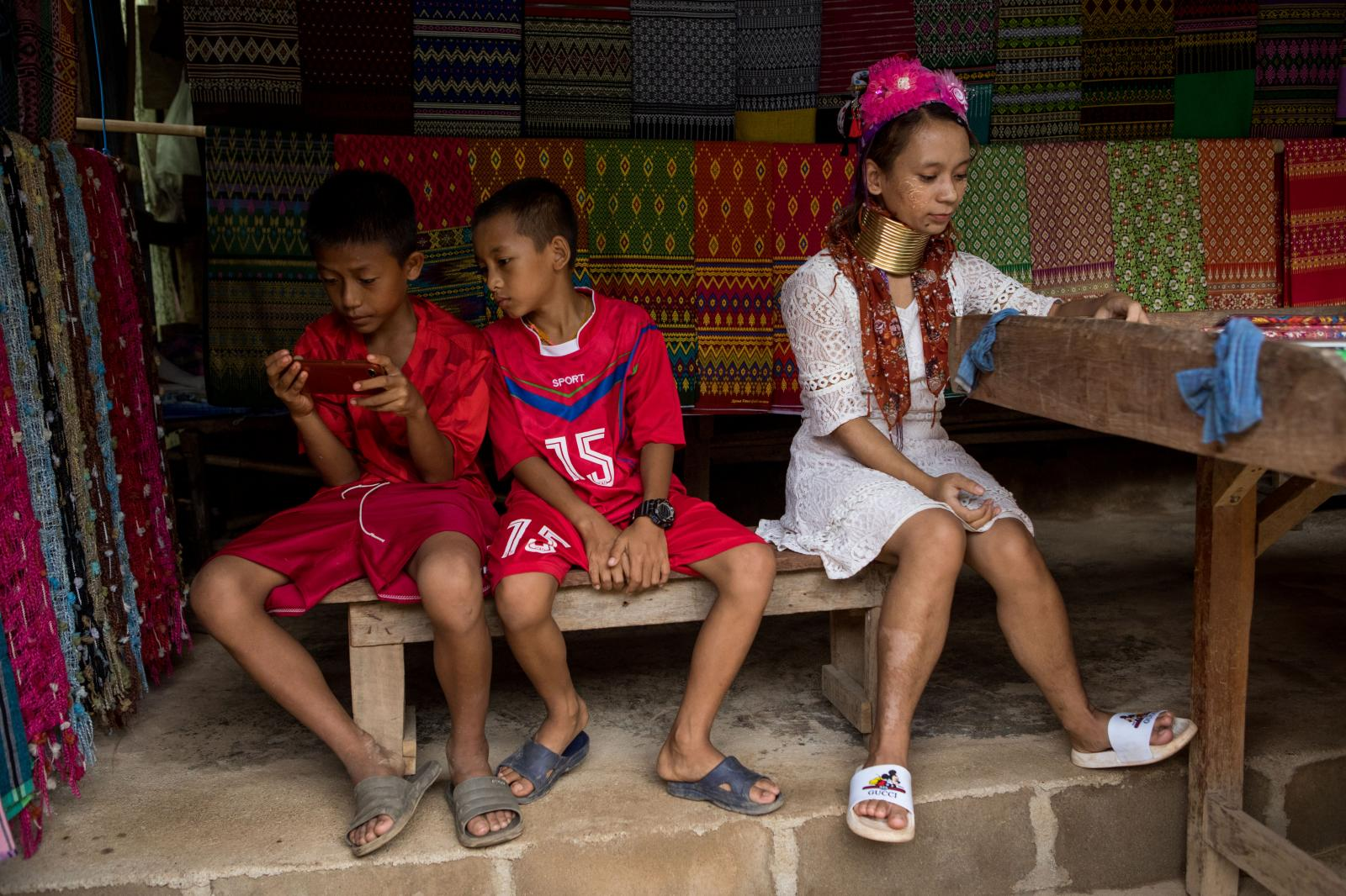 Mae Hong Son, Thailand � October 6, 2020 : Ma Nay, 20, plays on her phone next to her cousin (center) and his friend (left). The long neck village of Huai Suea Tao. Credit: Amanda Mustard for New York Times
