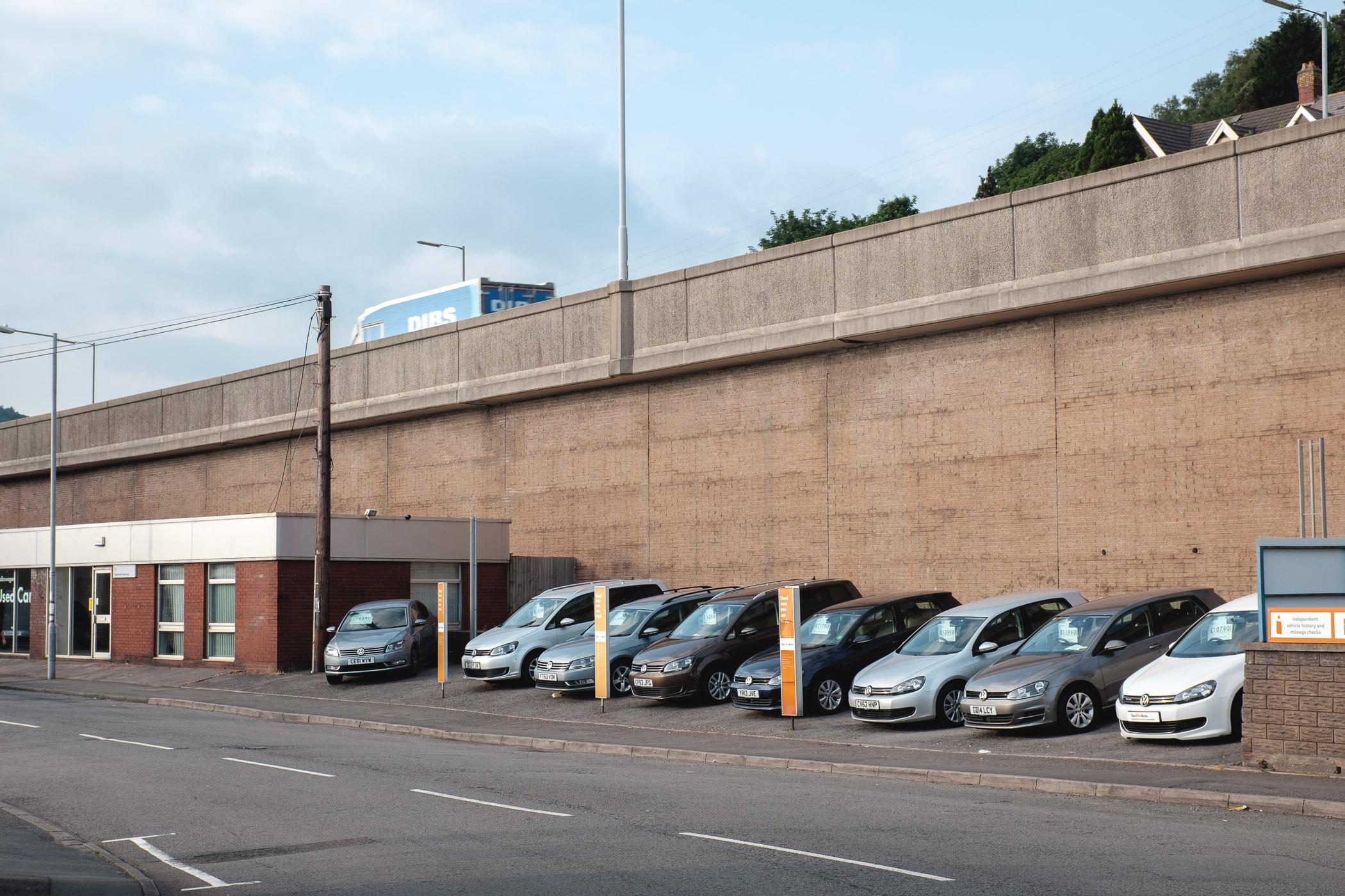 A car dealership in Port Talbot, on the site of the old Sinclair Garages. Businesses that were not demolished to make way for the motorway have had to adapt to it's often looming presence.