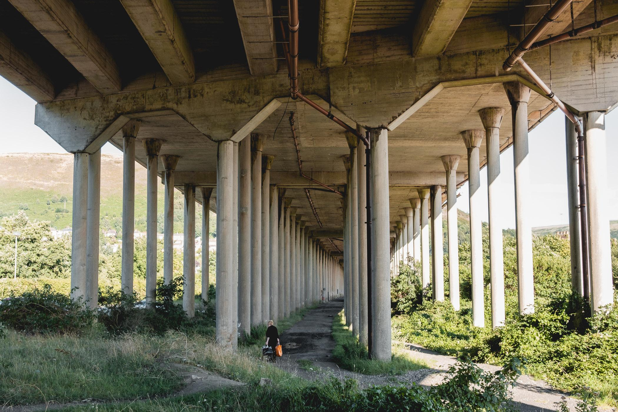 The concrete pillars used in some sections of the motorway were considered cutting edge technology at the time of its construction in the 1960s. Since then, the areas beneath have been taken back by both nature and residents. This section is a popular cycling and horse riding path.