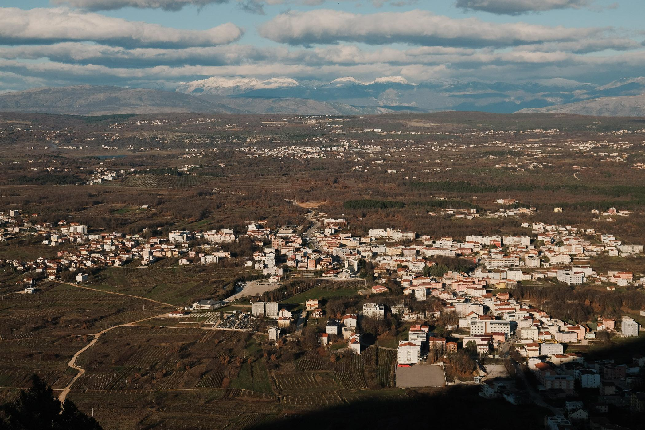 """The town of Medjugorje, whose Slavic name means """"between two mountains"""". The ethnically Croat town of around 4000 sits in the southern Herzegovina region of Bosnia, close to the border with neighbouring Croatia. The once quiet, rural town has taken on international fame since 1981, when six local teenagers allege to have been visited by an apparition of the Virgin Mary on a nearby hill."""