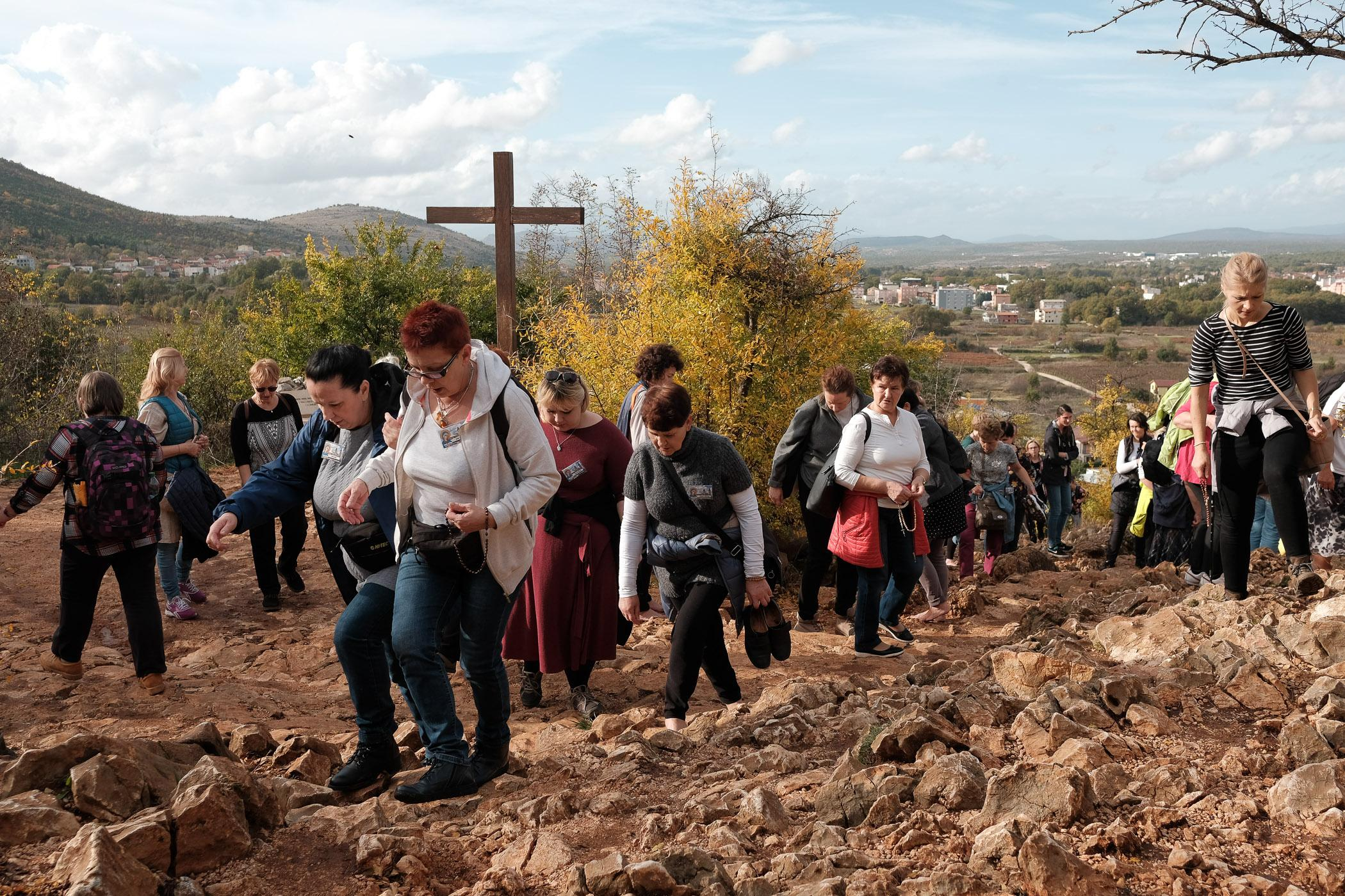 A group of Polish pilgrims treks up Apparition Hill on the outskirts of Medjugorje, Bosnia and Herzegovina, November 2019. In 1981, six local teenagers reported a visitation by the Virgin Mary, and have continued to experience regular communications with Her.
