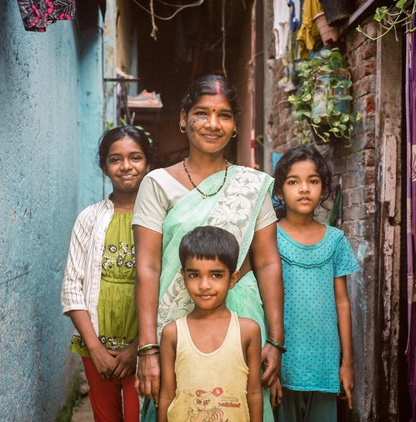 """Urmila Verma, 30, and her three children outside of their home in a settlement in Mumbai, India. Mrs. Verma migrated to Mumbai from Madhya Pradesh and began work as a maid. Before Covid came to India, she was working full-time in three homes, but with little job security and like many involved in India's informal sector, she was let go and now only has work in one household. Mrs. Verma's husband would normally help the family through daily wage work, which """"has all come to a standstill since lockdown"""" she said. Copyright © Sara Hylton/Redux Picutres, 2021"""