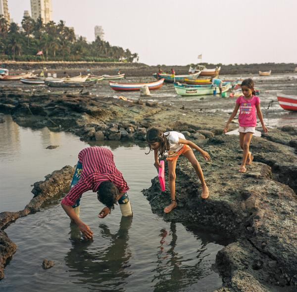 Gunwant Londhe (left) searches for crabs with his children on the shores of the Arabian Sea in Mumbai during India's devastating second wave. Copyright © Sara Hylton/Redux Picutres, 2021