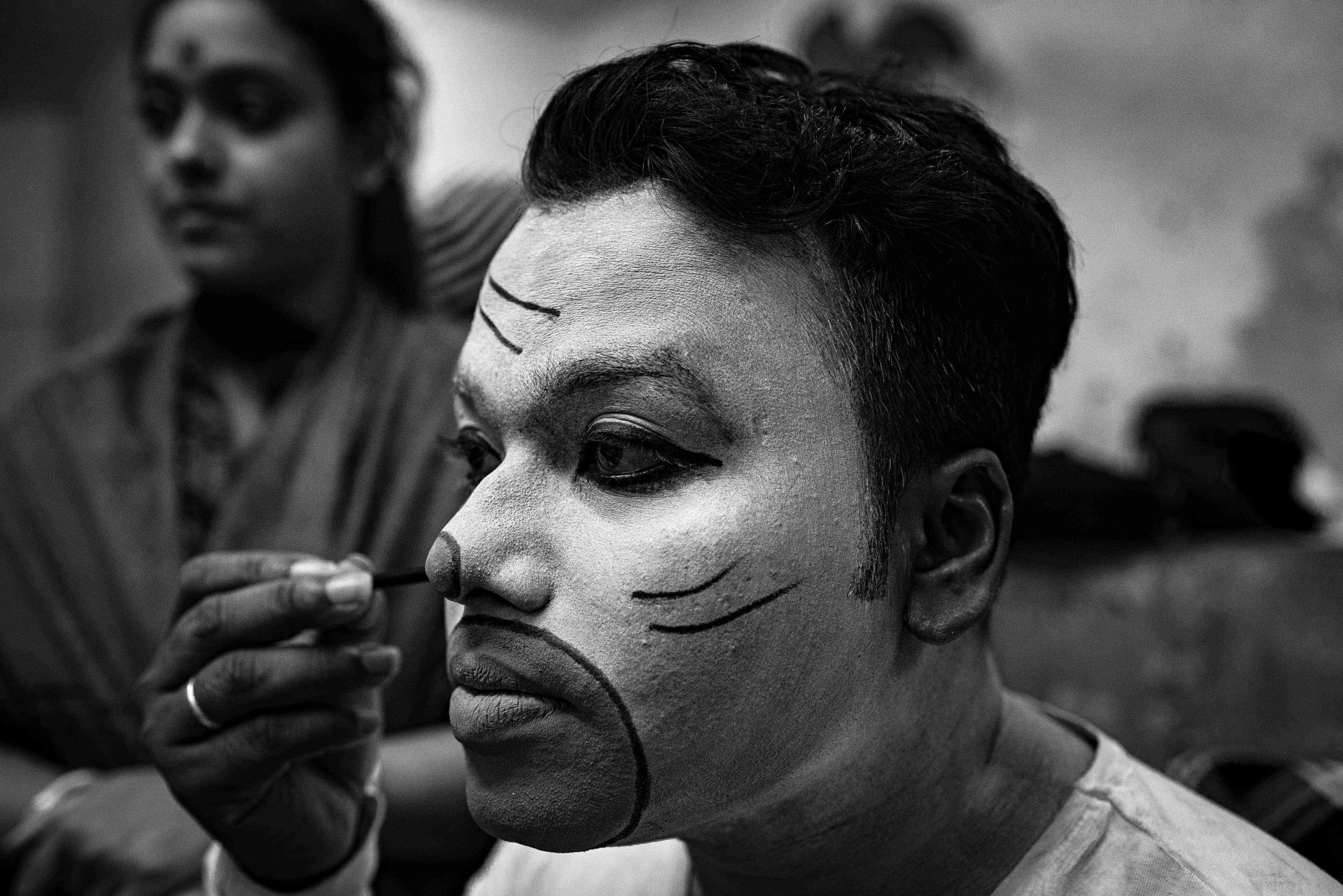 A performer taking makeup as per his role in the drama.