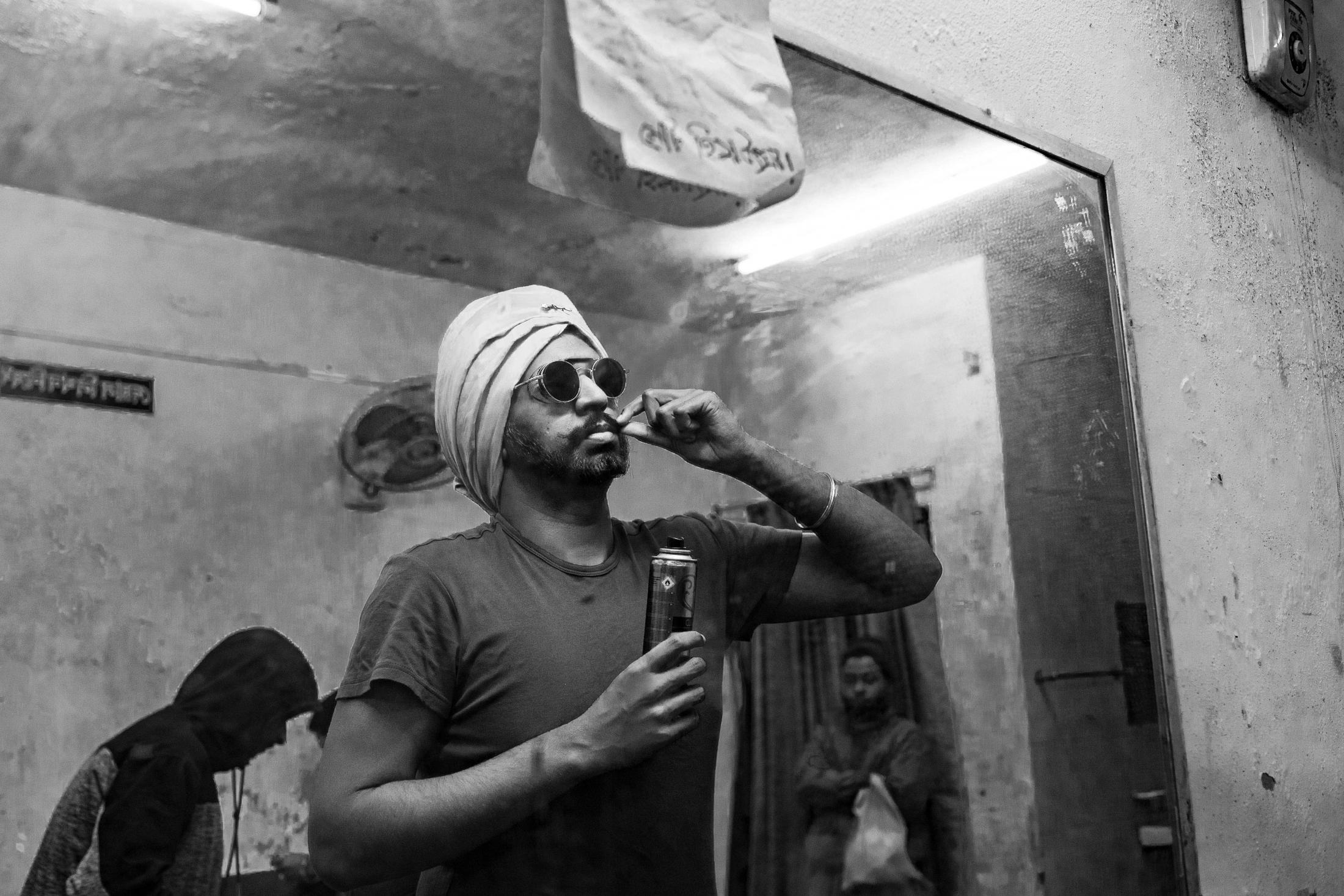 A performer checking his false mustache in front of the mirror.