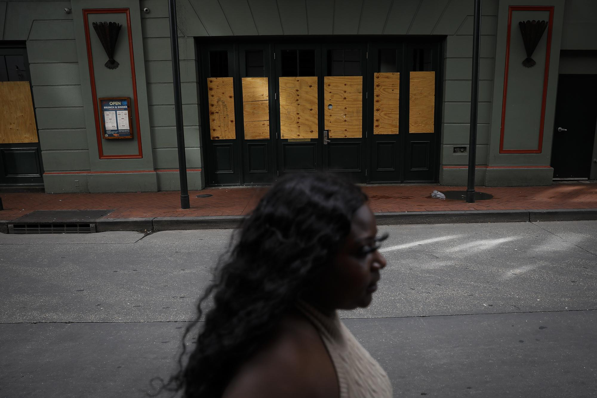 A woman walks past a restaurant boarded up with plywood in preparation for Hurricane Ida, in New Orleans, Lousiana, U.S. August 28, 2021. REUTERS/Marco Bello