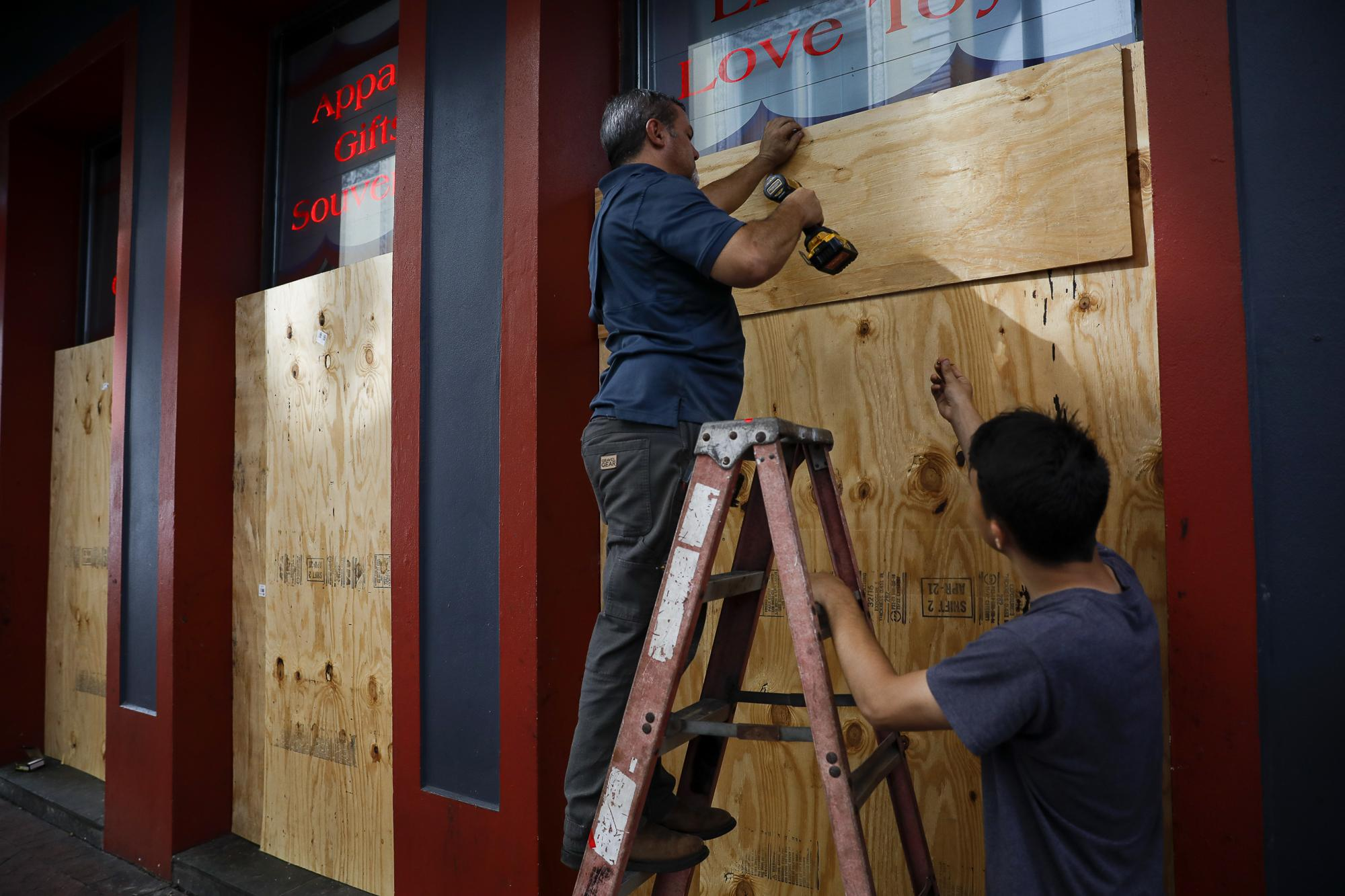 Men place plywood in front of a store in preparation for Hurricane Ida, in New Orleans, Lousiana, U.S. August 28, 2021. REUTERS/Marco Bello