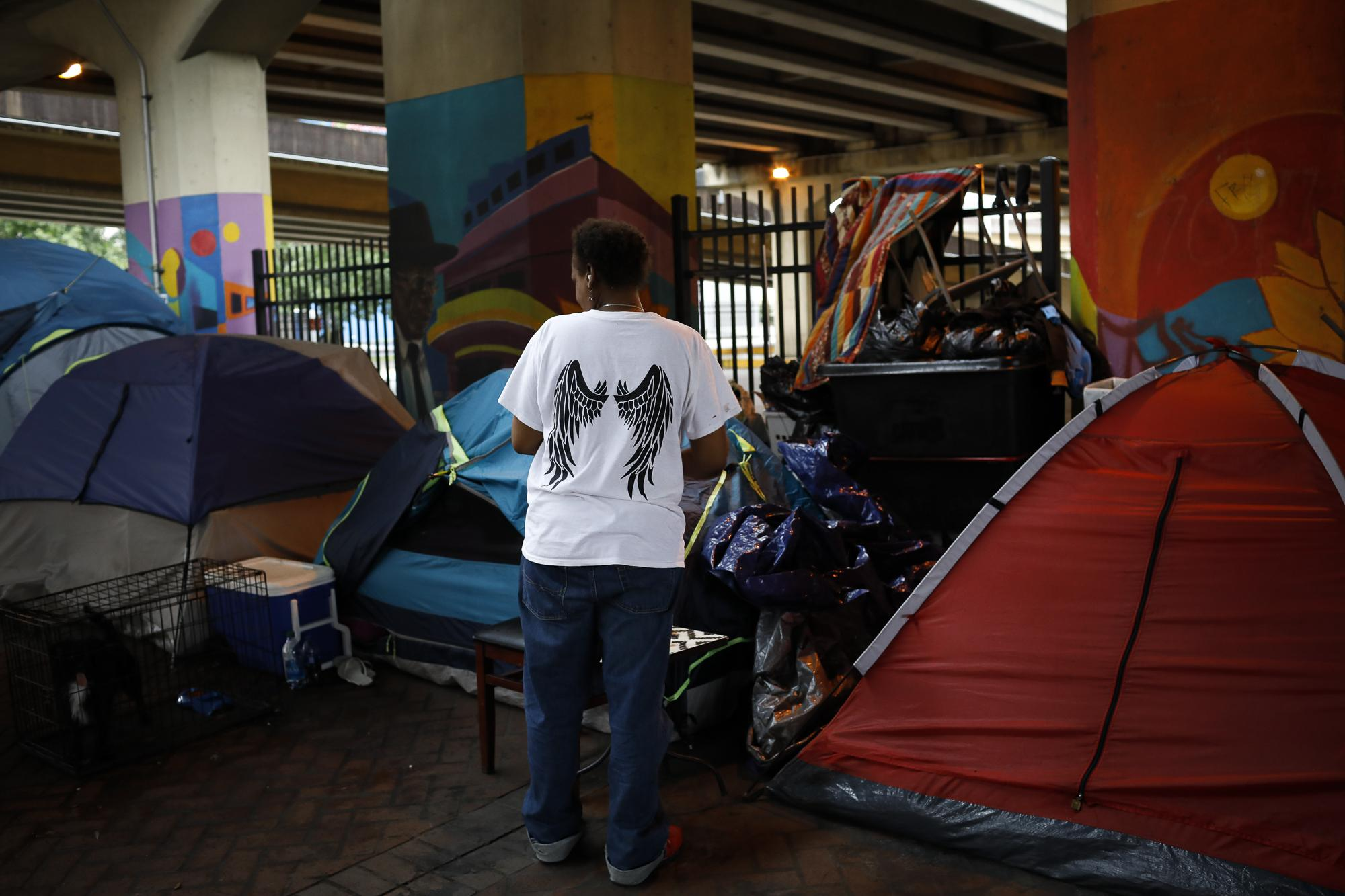 A homeless woman stands outside her tent under an expressway ahead of Hurricane Ida, in New Orleans, Louisiana, U.S. August 29, 2021. REUTERS/Marco Bello